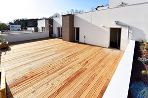 Zoom sur une grande terrasse finition bois avec jardinières végétalisées.